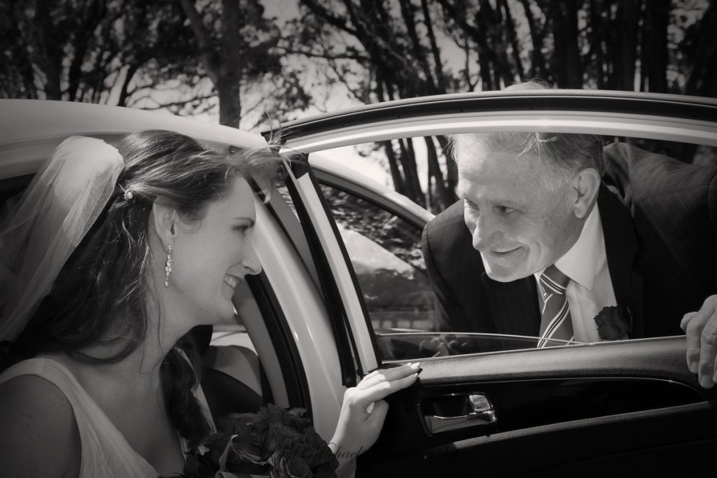 Dad helping bride out of the car